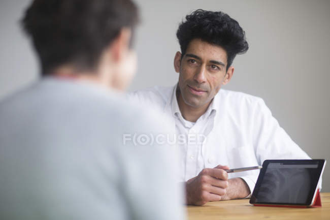 Doctor discussing X-ray on digital tablet with patient. — Stock Photo