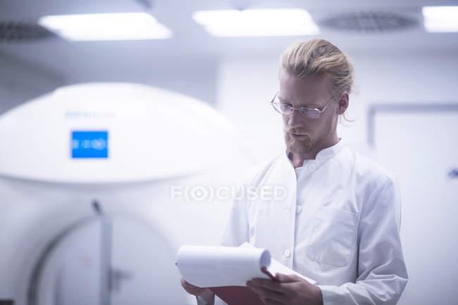 Рентгенолог перевірка примітки в радіології кімнаті. — стокове фото