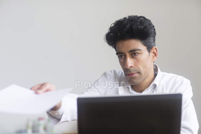 Doctor handing papers at desk with laptop. — Stock Photo