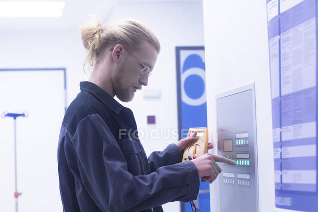 Electrician repairing switchbox in hospital. — Stock Photo
