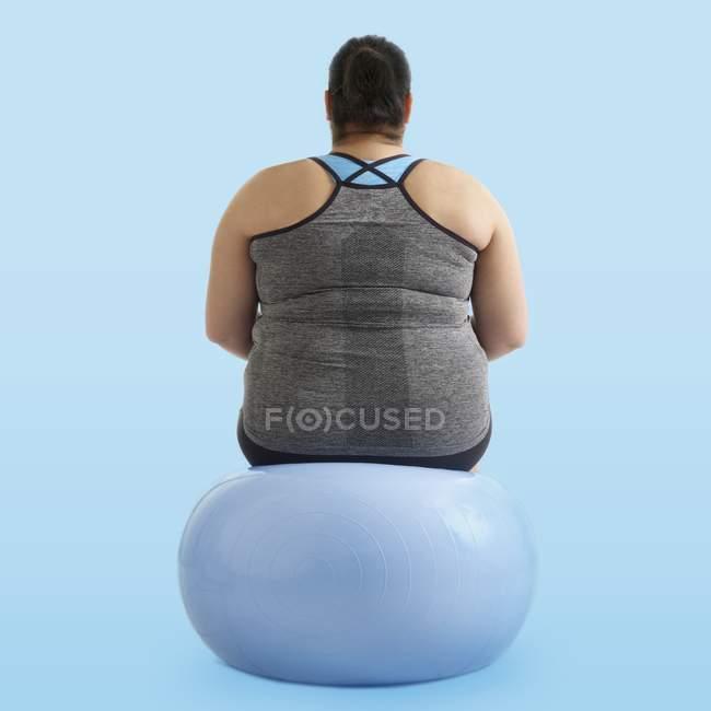 Mujer con sobrepeso sentada en la bola de ejercicio, vista trasera . - foto de stock
