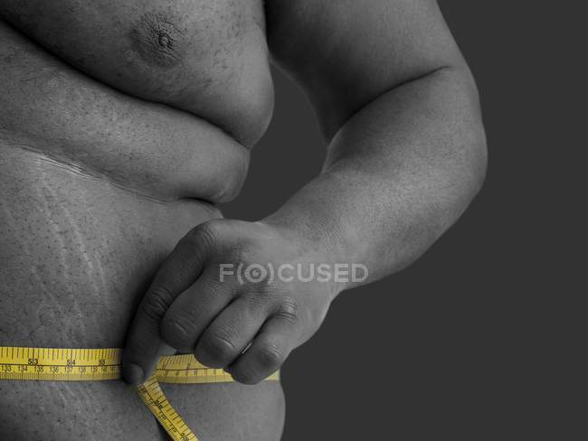 Overweight man measuring waist with tape measure. — Stock Photo