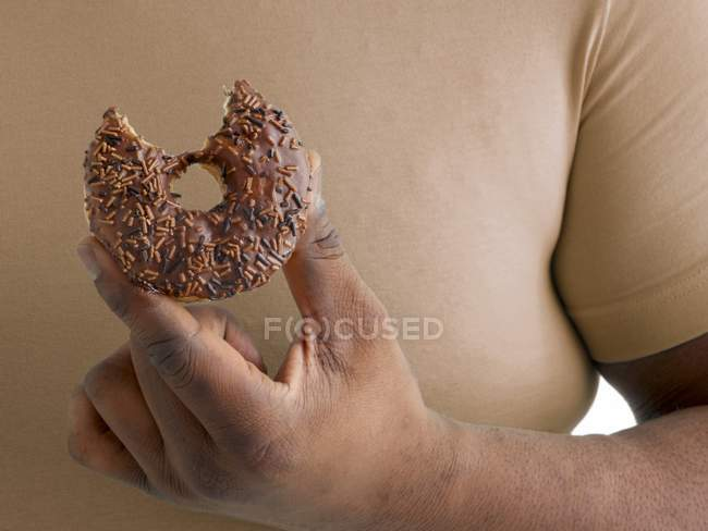 Overweight man holding doughnut with missing bite. — Stock Photo