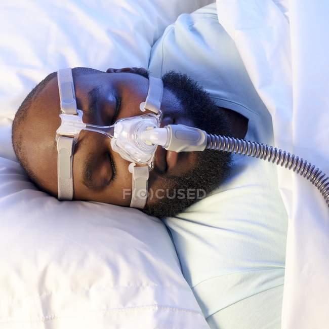 Uomo addormentato con ventilatore per il trattamento dell'apnea del sonno . — Foto stock