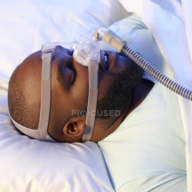 Homem adormecido usando ventilador para tratar a apneia do sono . — Fotografia de Stock