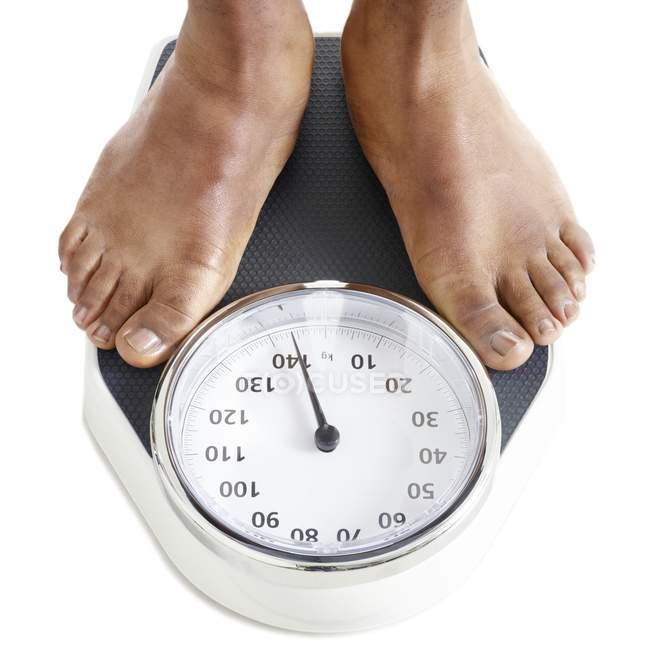 Vista recortada de los pies masculinos de pie sobre básculas de pesaje . - foto de stock