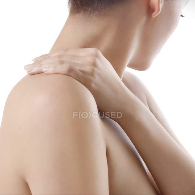 Mujer frotando hombros sobre fondo blanco. - foto de stock