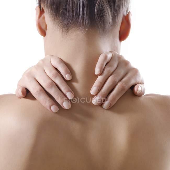 Mulher esfregando o pescoço no fundo branco — Fotografia de Stock