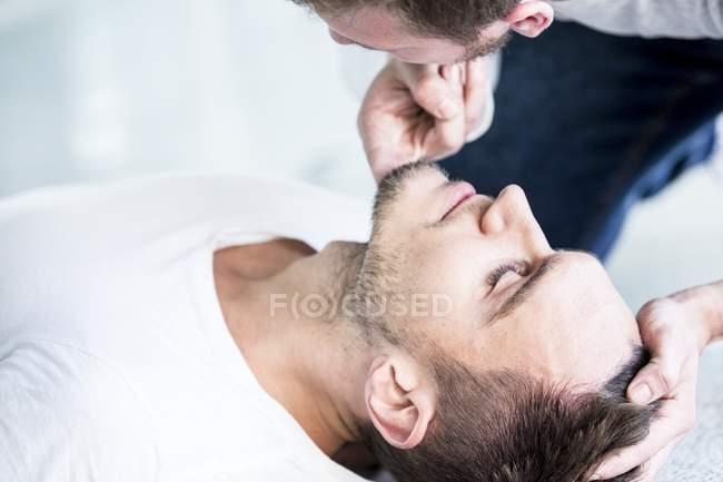 Врач-мужчина проверяет дыхание человека без сознания . — стоковое фото