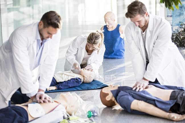 Doctors undertaking cardiopulmonary resuscitation training on dummies. — Stock Photo