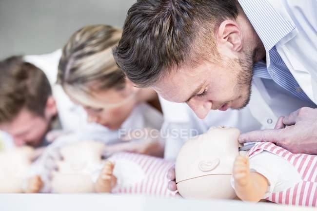 Médicos femeninos y masculinos practicando reanimación cardiopulmonar en maniquíes de entrenamiento infantil . - foto de stock