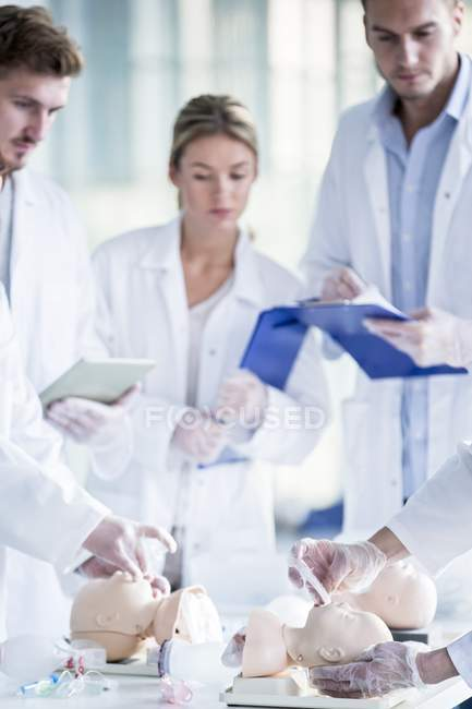 Doctors practicing tracheal intubation on infant training dummies. — Stock Photo