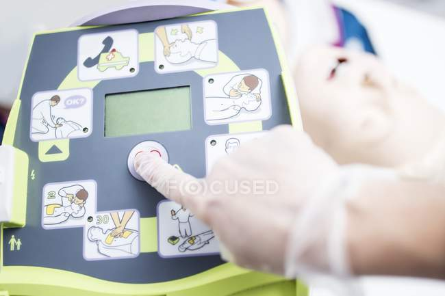 Doctor hand adjusting automated external defibrillator training. — Stock Photo