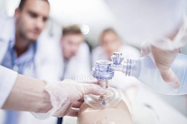 Médicos practicando la ventilación bolsa-válvula-máscara en maniquí de entrenamiento . - foto de stock