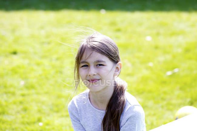 Smiling preteen girl posing in sunny park. — Stock Photo