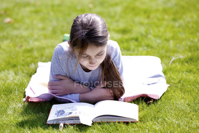 Preteen girl lying on blanket on green meadow in garden and reading book. — Stock Photo
