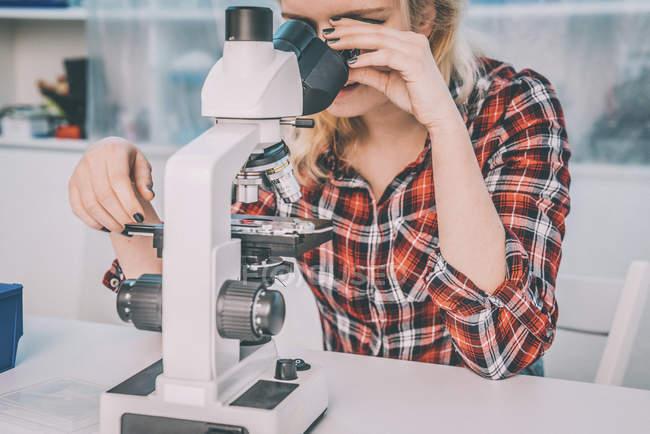 Estudante de biologia feminina usando microscópio no laboratório. — Fotografia de Stock
