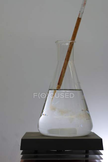 Close-up of pipette sampling chemical compounds from glass beaker. — Stock Photo