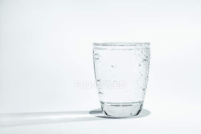 Vaso de agua con condensación sobre fondo blanco . - foto de stock