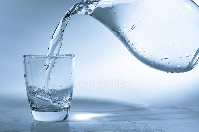 Pouring water into glass from jug on plain background. — Stock Photo