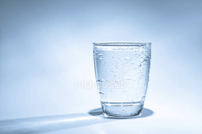 Glass of water with condensation on plain background. — Stock Photo