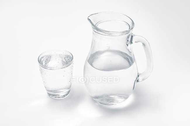 Glass and jug with drinking water on white background. — Stock Photo