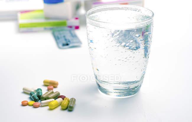 Varios medicamentos y vaso de agua en la mesa . - foto de stock