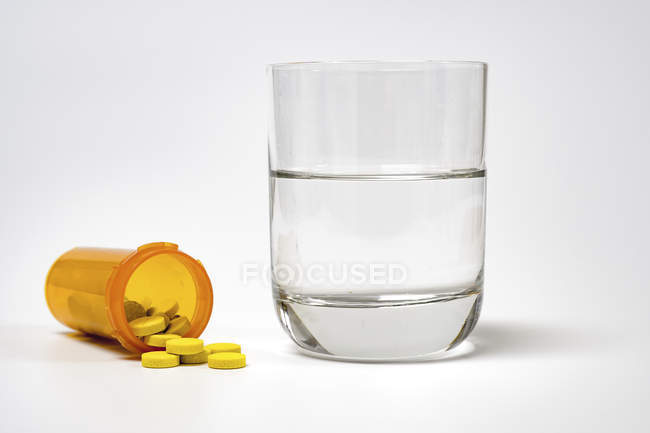 Лекарства и стакан воды на белом фоне . — стоковое фото