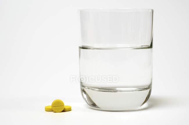 Таблетки и стакан воды на белом фоне . — стоковое фото