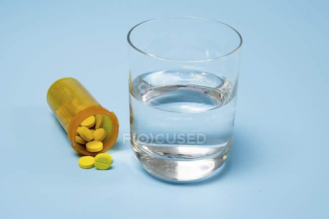 Medicamentos y vaso de agua sobre fondo azul . - foto de stock
