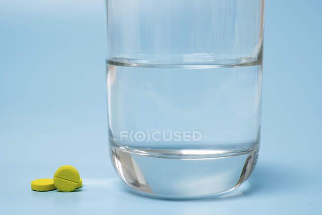 Pastillas y vaso de agua sobre fondo azul. - foto de stock