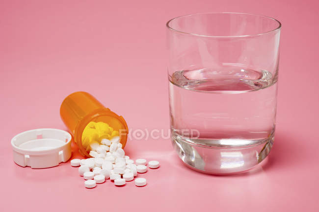Лекарства и стакан воды на розовом фоне . — стоковое фото