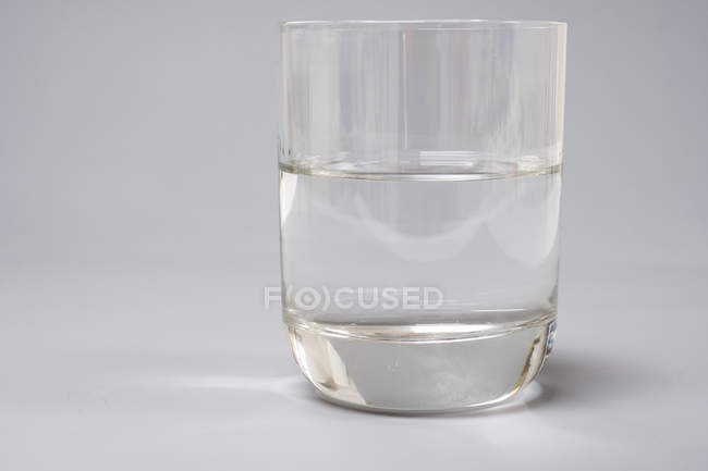 Glass of pure water on plain background. — Stock Photo