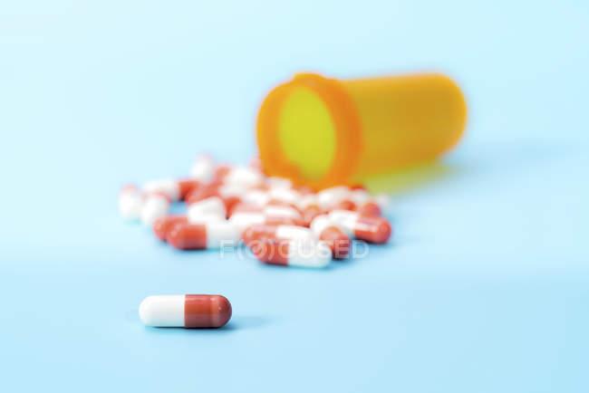 Капсулы с лекарствами, разливающиеся из пластиковой чашки на синем фоне . — стоковое фото