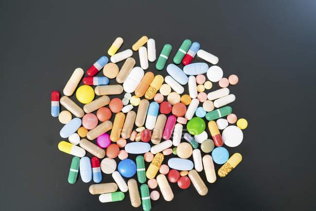 Pílulas e cápsulas multicoloridas em fundo preto . — Fotografia de Stock