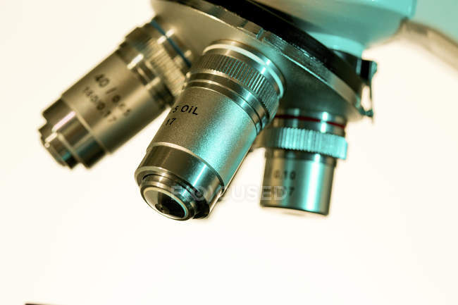 Close-up of light microscope lenses on white background. — Stock Photo