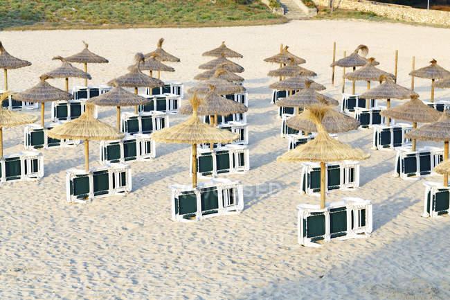 Шезлонгами и зонтиками на песчаном пляже. — стоковое фото