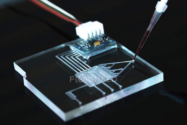Close-up of lab-on-a-chip integrated circuit device on black background. — Stock Photo