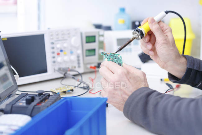 Close-up of technician repairing circuit board in electronics laboratory. — Stock Photo