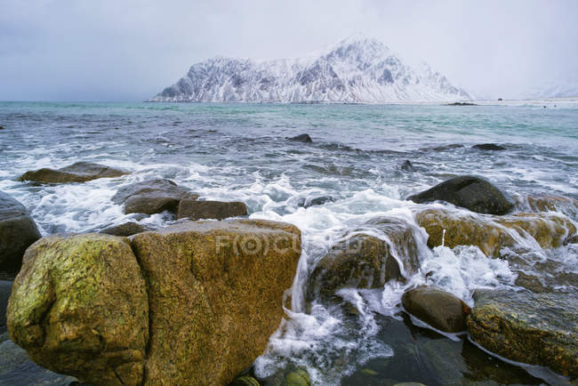 Rocky coastline with snow-capped mountains in distance. — Stock Photo