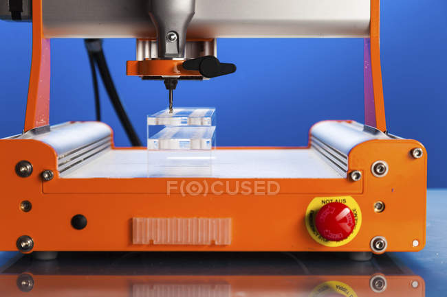 CNC milling machine drilling plastic block. — Stock Photo
