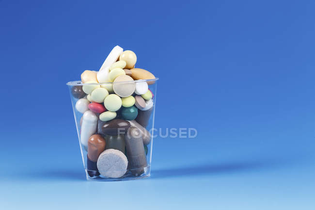 Ассорти таблетки в пластиковой чашке на синем фоне . — стоковое фото