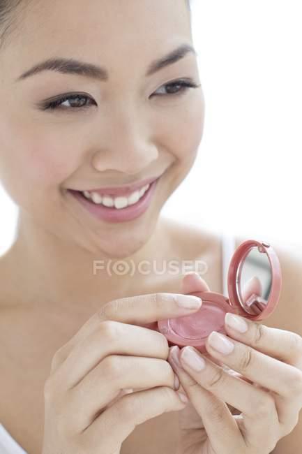 Молодой китайский женщина, применяя румяна на белом фоне — стоковое фото