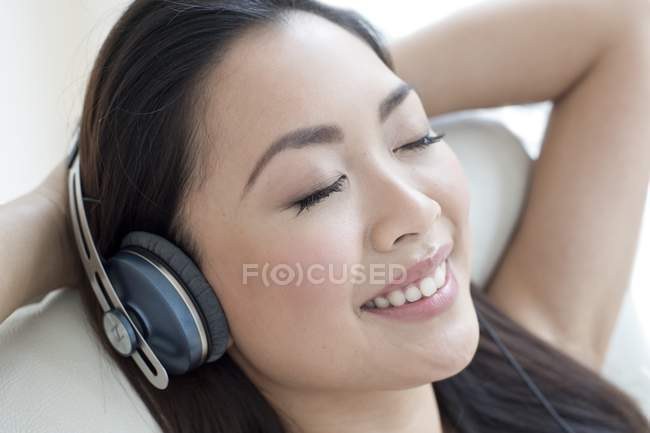 Asian woman listening to music in headphones with eyes closed. — Stock Photo