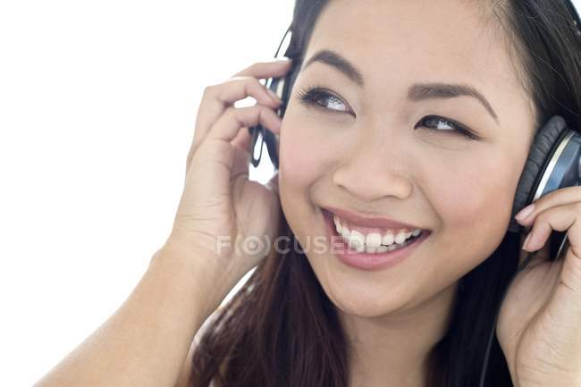 Portrait of cheerful young woman listening to music in headphones. — Stock Photo