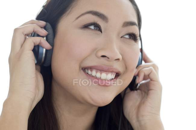 Portrait of female young adult listening to music in headphones. — Stock Photo