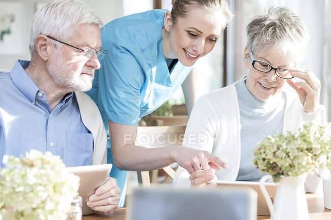 Senior adults using tablet computers in care home with nurse helping. — Stock Photo