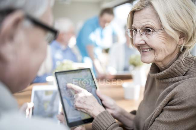 Senior adults looking at photo on digital tablet in care home. — Stock Photo