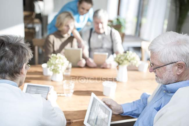 Senior adults using tablet computers at table with nurse helping in care home. — Stock Photo