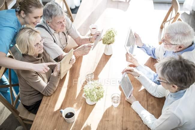 Vista ad alto angolo di adulti anziani che utilizzano computer tablet in casa di cura mentre il lavoratore aiuta . — Foto stock